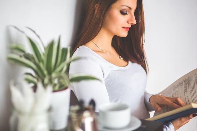 Nainen lukee kirjaa kotona